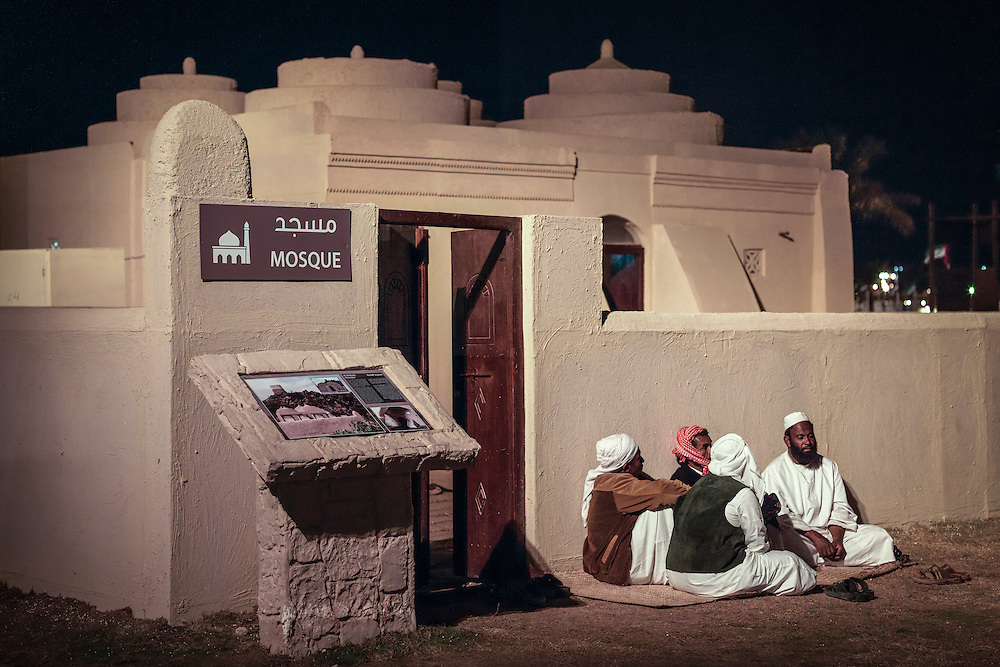 A small mosque remodelled after the Al Badiya Mosque, and a group of worshipers take rest at the outer wall.