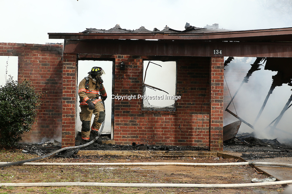 Adam Robison | BUY AT PHOTOS.DJOURNAL.COM<br /> A firefighter with the Verona Fire Department walks out of the home at 134 Presley Drive in Verona after battling a fire there on Monday morning.