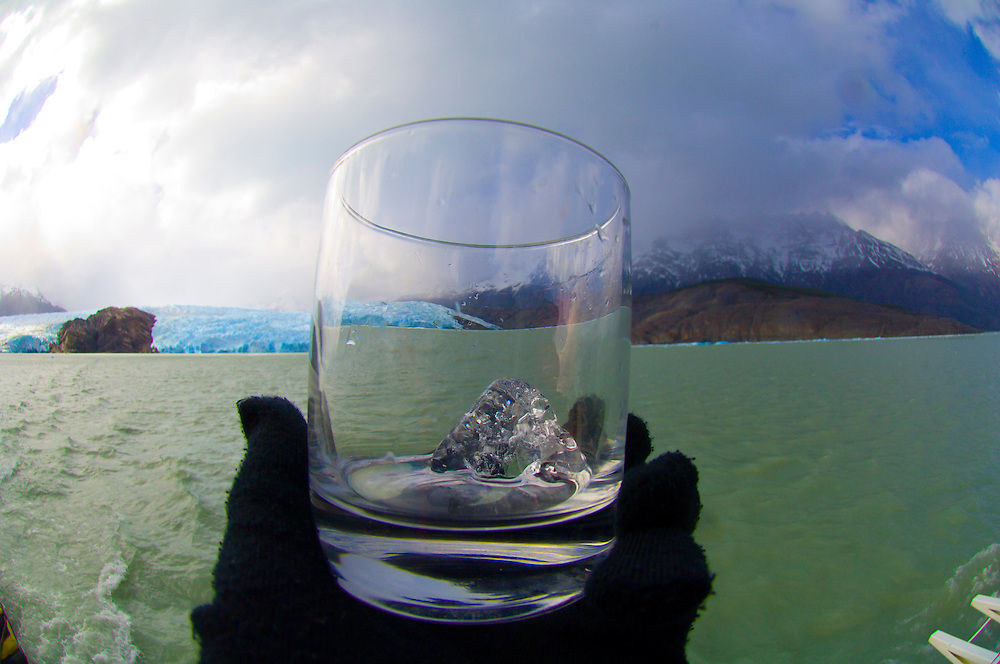 Glacier ice in a glass, Grey Lake (Lago Grey) with Grey Glacier and Paine Grande Mountain in background, Torres del Paine National Park, Patagonia, Chile
