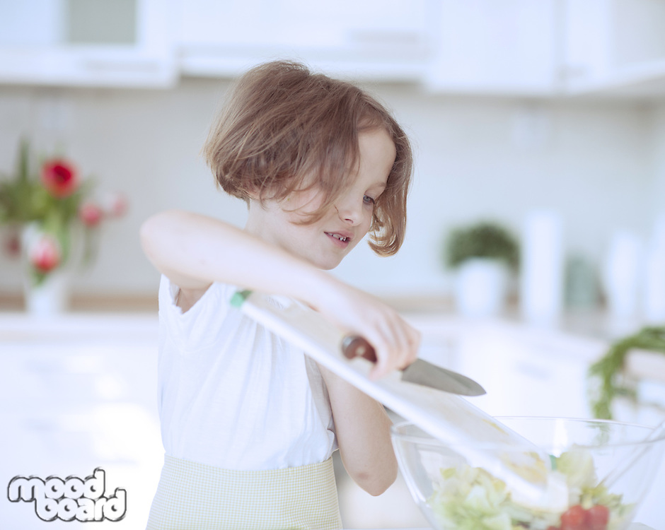 Young girl placing lettuce in salad bowl using a knife