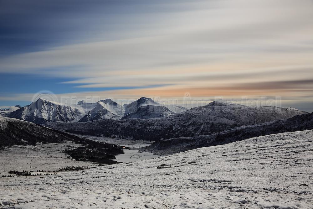 Full moon snowlandscape with view over water and mountains. Long exposure with blurred skies | Fullmåne og snølandskap med utsikt mot vann og fjell. Lang eksponering med utdratt skyer.