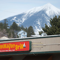 Humphreys Peak can be seen above the sign for Himalayan Grill in Flagstaff Thursday.
