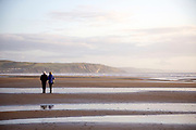 BORTH, WALES, UK 16TH MARCH 2020 - Elderly couple walking along Borth beach during early morning sunrise light, County of Ceredigion, Mid Wales, UK.