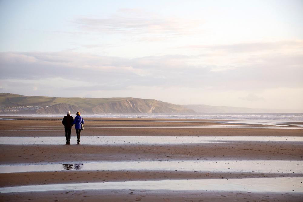 BORTH, WALES, UK 16TH MARCH 2020 - Elderly couple walking along Borth beach during early morning sunrise light, County of Ceredigion, Mid Wales, UK.