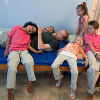 Lee Spearman takes a break during his physical therapy with his children Levi, 6, Molly, 7, Mia, 6, Gabby, 10, and Dee, 10,  at First Step Therapy in Wilmington, N.C., April 24, 2014. Lee Spearman was hospitalized in December of 2013 with an infection that was ravaging his body and almost took his life and resulted in having both of his legs amputated below the knee and all the fingers on his left hand. Photo By Mike Spencer/StarNews Media