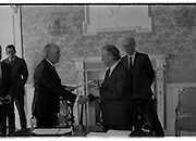 Charles Haughey Receives Seal Of Office.   (T3)..1989..12.07.1989..07.12.1989..12th July 1989..After winning the General Election and having been elected Taoiseach by a majority in Dail Eireann, Charles Haughey went to Aras an Uachtarain to accept the seal of office. The seal of office was granted by President Patrick Hillery...Image shows President Patrick Hillery being the first to congratulate  An Taoiseach, Charles Haughey,after signing the official paperwork watched by  Mr Michael O'hOdhran, Secretary to President Hillery and Mr Dermot Nally, Secretary to the government