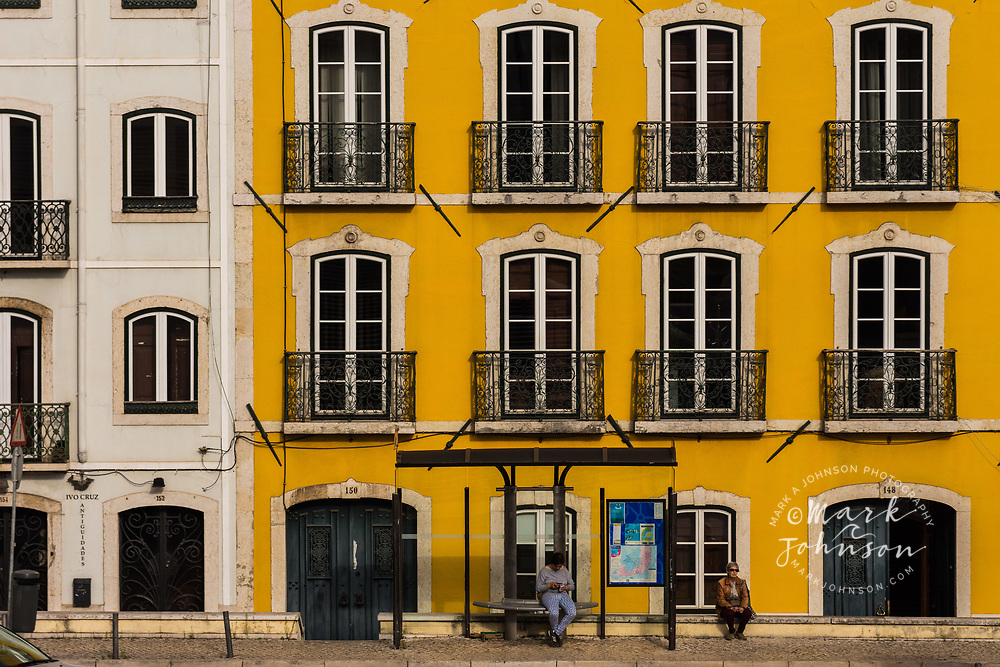 Women waiting at a bus stop in front of a bright yellow building, Lisbon, Portugal