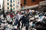 ITALY, NAPLES : Children  walk through uncollected garbage at the exit of school in  downtown Naples in the historic Spanish district on November 22, 2010. Naples latest garbage emergency is getting worst day after day and piles of garbage are seen all over the italian souther city. AFP PHOTO / ROBERTO SALOMONE