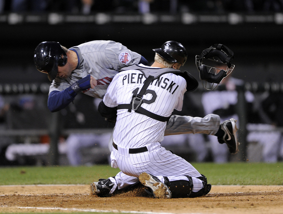CHICAGO - SEPTEMBER 30:  Michael Cuddyer #5 of the Minnesota Twins slams into catcher A.J. Pierzynski #12 in the 5th inning of the game against the Minnesota Twins at U.S. Cellular Field in Chicago, Illinois on September 30, 2008.  Pierzynski held onto the ball to record the third out of the inning.  The White Sox defeated the Twins 1-0 to win the American League Central title.  The Sox and Twins had to play a one game playoff to determine the American League Central Champion.  (Photo by Ron Vesely)