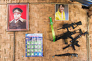 Myanmar. Aung San Suu Kyi portrait on wall of a food stall. With plastic guns and knives.