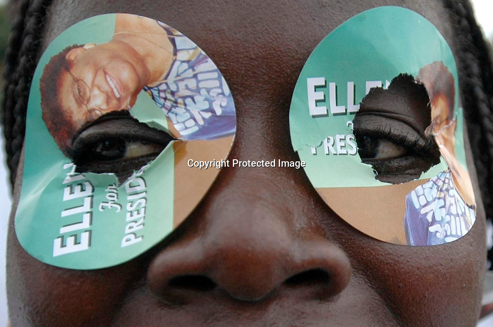 A supporter of Liberian presidential candidate Ellen Johnson Sirleaf wears campaign stickers over her eyes as she walks in a parade with Sirleaf in Monrovia, Liberia, October 6, 2005.