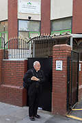 Following the attack on a group of Muslim men outside the Finsbury Park mosque which killed one person and seriously injured another ten, an Anglican minister stands outside the Islamic building where a temporary sign shows where to pray during thew disruption, on 19th June 2017, in the borough of Islington, north London, England.