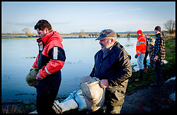 Burrowbridge, Somerset, United Kingdom.Sunday, 9th February 2014. Members of the Somerset Levels Community near  Burrow Bridge unload sand bags to an area that is on the verge of flooding.  The levels have been flooded since the start of 2014, with people being forced to leave their homes. Picture by Andrew Parsons / i-Images