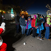 Tonya Slim (center), 8, and Laurie Pahe (right), 7, wave at Santa as they stand in line for fruit and other goodies after the tree lighting, Saturday Nov. 24 in Gallup at the McKinley County Courthouse Square.