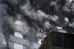© Licensed to London News Pictures. 14/06/2017. London, UK. A resident looks from his balcony directly below the building Grenfell Tower at the Lancaster West Estate -  scene of a huge fire in west London. The blaze engulfed the 27-storey building with 200 firefighters attending the scene. A number of fatalities have been reported. Photo credit: Peter Macdiarmid/LNP