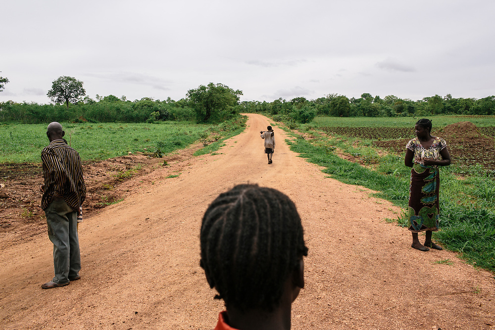 A boy heads home after a lesson at a demo site which is growing maize, ground nuts, soy beans, and sunflowers in Sisinje agriculture camp in the Kamoto Village. Local farmers are learning new, modern techniques taught by their community agriculture dealers. These new methods will help produce more crops. The crops from the same camp are then all put together to be sold to buyers at higher volumes, making the village more money. There are 140 agriculture dealers, managing 690 demo plots with 106 farmers per plot.