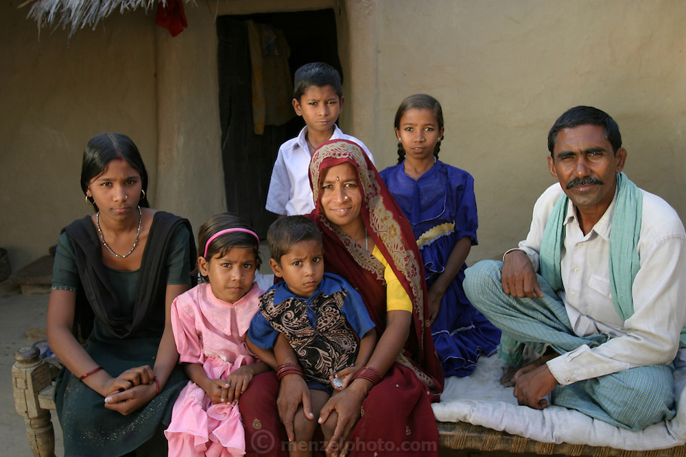 Yadav family portrait in the courtyard of their home during revisit with the family, 2004. Ahraura Village, Uttar Pradesh, India. The Yadavs were India's participants in Material World: A Global Family Portrait, 1994 (pages: 64-65), for which they took all of their possessions out of their house for a family-and-possessions-portrait. Child, Children..