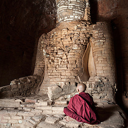 Young monk sitting in front of an old statue of Buddha, Bagan, Myanmar, Asia.