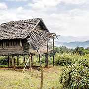 A damaged wooden rice hut sits on stilts in Northern Laos.