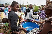 A woman shops for plastic containers during a non-food item fair in the Miketo IDP settlement, Katanga province, Democratic Republic of Congo on Sunday February 19, 2012. Displaced people who have lost most of their belongings as they fleed their homes receive coupons their can exchange for goods at a fair held in partnership with local traders.