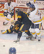 Canisius Griffins Carl Hudson (center) battles with LSSU Lakers Rick Schofield (right) while goalkeeper Dan Morrison (#30) keeps an eye on a loose puck during the third period of the Griffins 5-4 loss to Lakers Friday night in Sault Ste. Marie, MI.