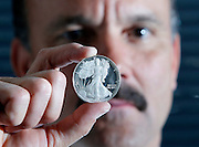 Craig Franco, founder of the Utah Gold and Silver Depository, holds a Liberty Silver Dollar at his office in Salt Lake City, Friday, May 6, 2011. Utah is the first state in the country to legalize gold and silver coins as currency, allowing the state's consumers to use the precious medals to open checking accounts instead of Federal Reserve notes. (AP Photo/Colin E Braley)