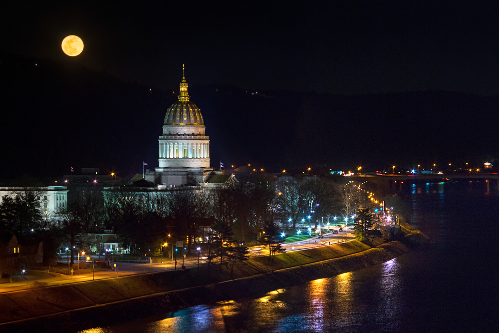 A full yellow moon is seen rising above the gold adorned capitol building of Charleston, West Virginia at night.