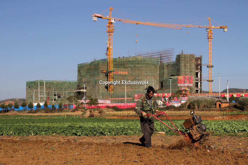 CHENGGONG, CHINA -China Out - Finland Out<br /> <br /> Ghost City <br /> <br /> A farmer works in a field in front of a construction site on November 21, 2013 in Chenggong, Yunnan Province of China. Chenggong is a satellite city located just south of Kunming. As of 2012, much of the newly constructed housing in Chenggong is still unoccupied, and it is reportedly one of the largest ghost towns in Asia. According to a China Youth Daily report in July, at least 12 such ghost cities across the country have been found. Besides the best known of these - Ordos in North China's Inner Mongolia Autonomous Region, the list also included Changzhou in Jiangsu, Zhengdong New Area in Henan Province, Shiyan in Hubei and Chenggong District of Kunming in Yunnan.<br /> ©Exclusivepix