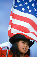 A Navajo cowgirl carries the American Flag as she prepares to enter the arena for the opening ceremonies of the Kayenta Rodeo, which include the national anthem and a prayer in Navajo. Competitors and spectators drive long distances across the Navajo Nation to participate in the Kayenta Rodeo. The Navajo Nation, home to approximately 175,000 people, encompasses 25,000 square miles spanning the Arizona – New Mexico border and a sliver of southeastern Utah.
