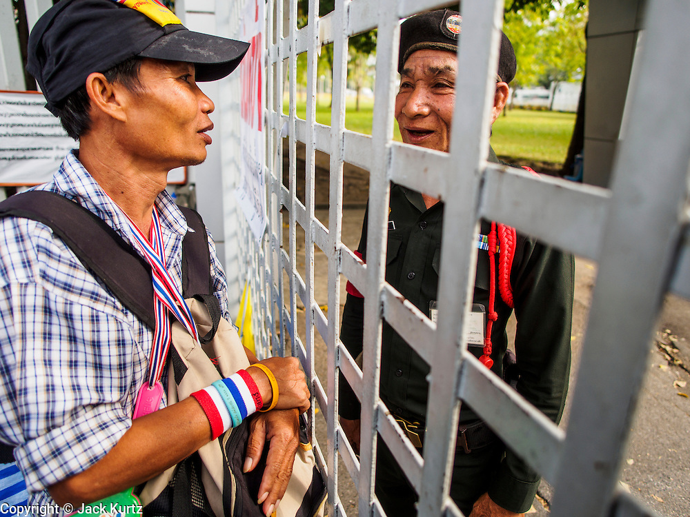 24 DECEMBER 2013 - BANGKOK, THAILAND:   An anti-government protestor talks through the gate to a police officer inside the Thai-Japan Stadium grounds. Hundreds of anti-government protestors are camped out around the Thai-Japan Stadium in Bangkok, where political parties are supposed to register for the election on February 2. As of Dec 24, nine of the more than 30 parties were able to register. Protestors hope to prevent the election. The action is a part of the ongoing protests in Bangkok that have caused the dissolution of the elected government.    PHOTO BY JACK KURTZ