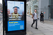 Two Londoners - one wearing a face covering, and the other choosing not to, walk past a bus stop ad promoting basic personal hygiene like handwashibng,  in Victoria during the Coronavirus pandemic, on 6th August 2020, in London, England.