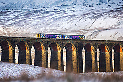 © Licensed to London News Pictures. 22/01/2019. Gearstones UK. A train crosses Ribblehead Viaduct in the snow covered shadow of Whernside Mountain this morning after a night of snow fall in the Yorkshire Dales. Photo credit: Andrew McCaren/LNP