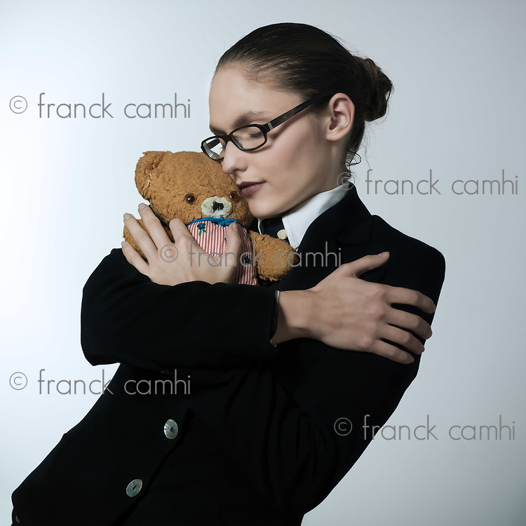 studio shot portrait of a beautiful young woman in a costume suit holding a teddy bear