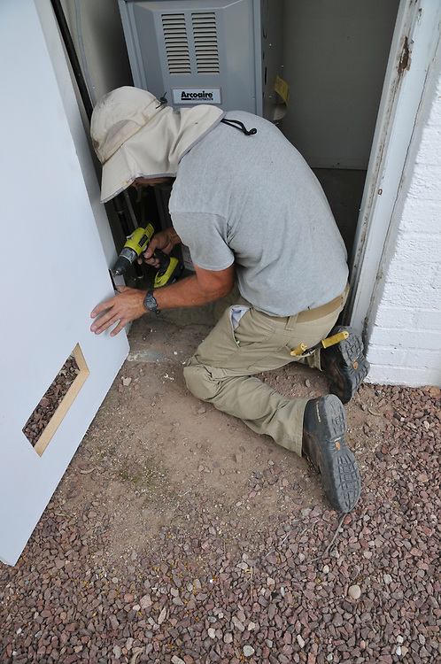 My home renovation project includes a heating and cooling upgrade. And the HVAC company wasn't pleased with my new solid-core furnace room door. So, Jesse Micander returned, removed the door, cut a couple of holes in it, and now he's re-installing.