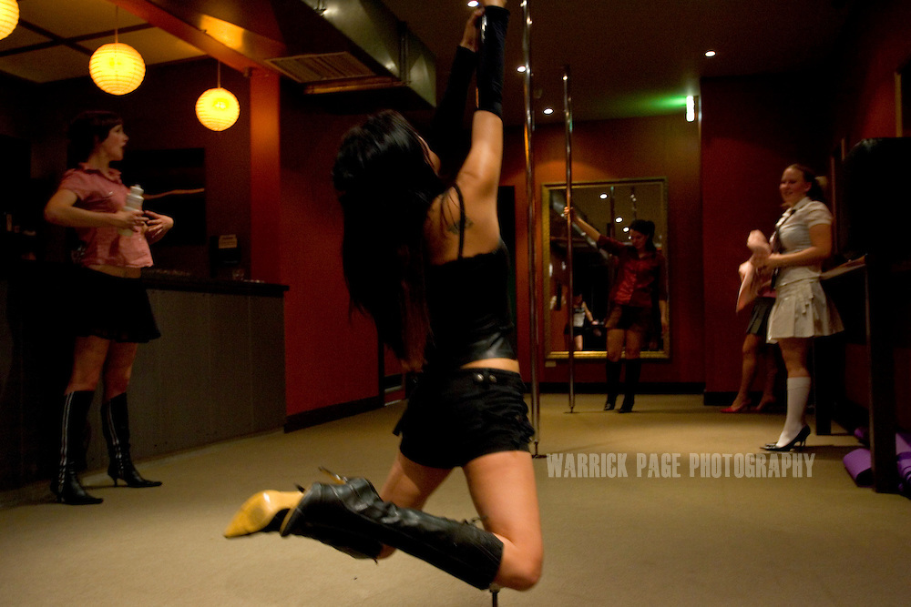 "MELBOURNE, AUSTRALIA - AUGUST 10: Lana Turner (C), 32, practices a move during a beginners pole-dancing class at the Imperial Hotel, August 10, 2006, Melbourne, Australia. Lana, a full-time mother of two, decided she wanted to get fit after having her children and took up pole dancing because ""it's fun and addictive"". Previously reserved for strip clubs, pole dancing is now quickly becoming a new fitness crazy throughout Australia, Europe and the US with thousands of women from all walks of life leaving traditional gymnasiums for the more social and challenging art of pole dancing. Pole dancing for fitness exploded onto the public scene after celebrities such as Angelina Jolie, Jennifer Anniston and Britney Spears professed it was their favourite form of exercise. Classes are often small in numbers giving a more personal atmosphere and strong bonds of friendship are often formed between students and instructors. Instructors claim a noticeable increase in their students' self-confidence after only a few weeks. Most students claim even thought it's a rigorous workout, they're having so much fun it doesn't feel like exercise at all. According to ""Polestars"", a British company that began setting up classes throughout six Australian cities in 2004,  ""a good session on the pole"" can burn more calories than at the gym and provide more muscle tone.  (Photo by Warrick Page)"