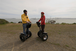 Couple on Segways, each on a Segway, on Angel Island State Park in San Francisco Bay, California, CA. Model released..Photo camari215-70540..Photo copyright Lee Foster, www.fostertravel.com, 510-549-2202, lee@fostertravel.com.