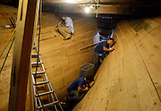 "Shipwrights Nick Bellico, Matt Morello and James Kirscher trim ""gump wedges"" in the hold of the Charles W. Morgan at the Mystic Seaport H.B. duPont Preservation Shipyard Tuesday, July 2, 2013. The work on the 19th century whaleship, the last remaining wooden whaling ship remaining and the oldest American commercial vessel still in existence as well as a National Historic Landmark, is slated to be re-launched on July 21st this summer and embark on its 38th voyage, a tour of historic New England ports in the spring of 2014. . (Sean D. Elliot/The Day)"