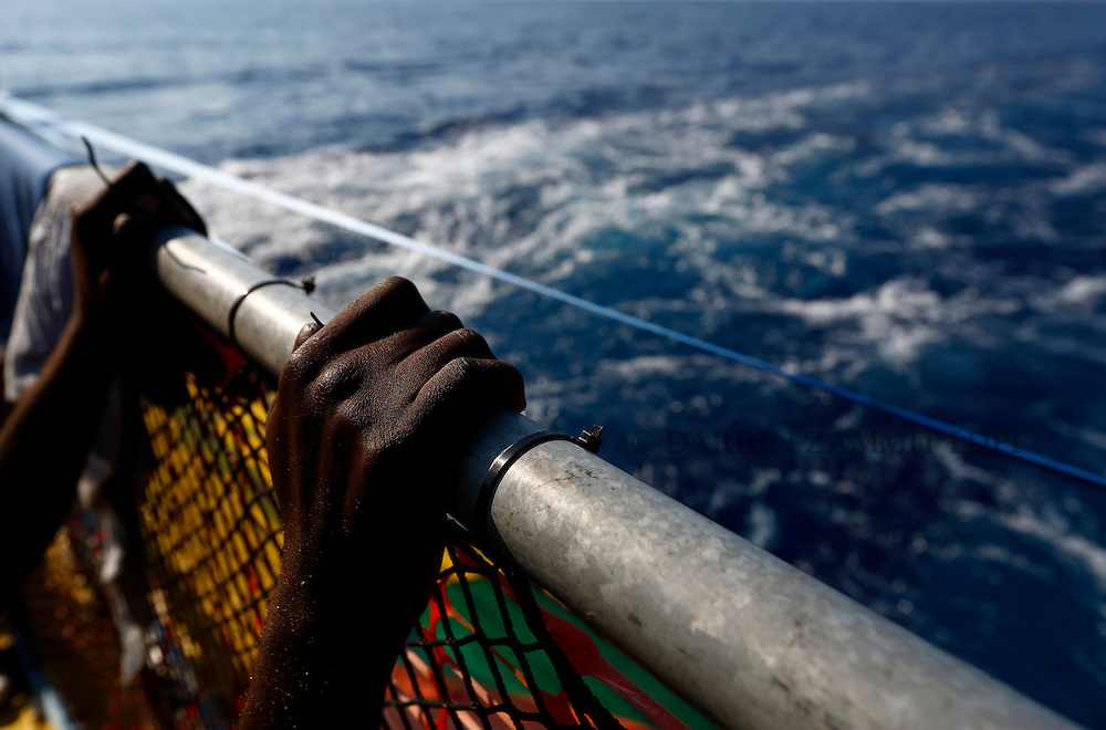 A migrant holds onto a railing at the stern of the Medecins san Frontiere (MSF) rescue ship Bourbon Argos somewhere between Libya and Sicily August 8, 2015.  Some 241 mostly West African migrants on the ship are expected to arrive on the Italian island of Sicily on Sunday morning, according to MSF.<br /> REUTERS/Darrin Zammit Lupi <br /> MALTA OUT. NO COMMERCIAL OR EDITORIAL SALES IN MALTA