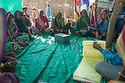Sheela and her local farmer training school meet to share their loan money and learn about making organic fertiliser for their farms at a farmer field school, Sendhwa, India.