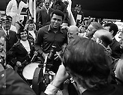 Muhammad Ali In Dublin..1972..11.07.1972..07.11.1972..11th July 1972..Prior to his fight against Al 'Blue' Lewis at Croke Park ,Dublin, former World Heavyweight Champion,Muhammad Ali arrives at Dublin Airport..The fight was part of his build up for for a championship fight against the current World Champion, 'Smokin'  Joe Frazier. Ali had been stripped of the title partly due to his refusal to join the American military during The Vietnam War,which he had opposed...Photo of Muhammad Ali being mobbed by fans and the media on the tarmac at Dublin Airport. Included in the picture are some members of The Emerald Girls Pipe Band.