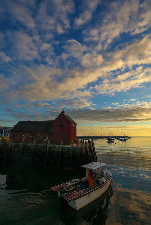 New England harbor scenery of a fishing boat leaving safe harbor with Motif #1, a famous red fishing shack in Rockport, Massachusetts on Cape Ann. The photo captures the local fishing boat with the iconic landmark and a stunningly beautiful sunrise sky. The historic landmark is known throughout New England as Motif #1, so called because it is the most often painted building in America.<br />