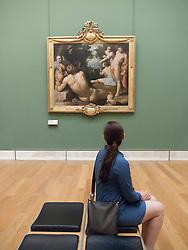 Woman looking at painting Le Bapteme du Christ by Cornelius van Haarlem at The Louvre museum in Paris France