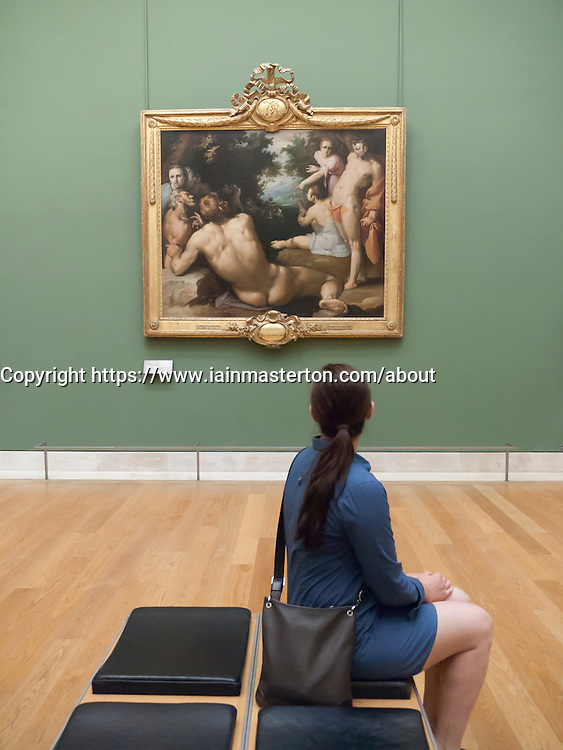 Woman looking at painting Le Bapteme du Christ by Cornelius van Haarlem at The Louvre museum in Paris France