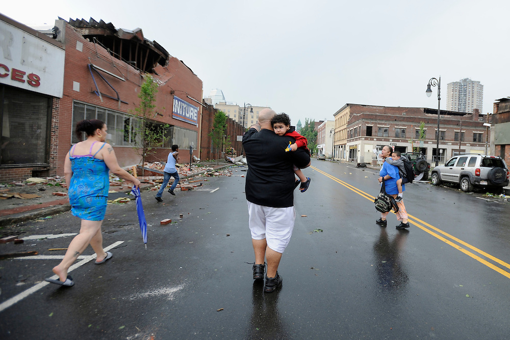 People seek cover after an announcement of another possible tornado in Springfield, Mass.  A tornado struck downtown Springfield, one of Massachusetts' largest cities, scattering debris, toppling trees, and frightening workers and residents. (AP Photo/Jessica Hill)