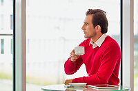 Portrait of thougtful businessman sitting while drinking coffee in lobby