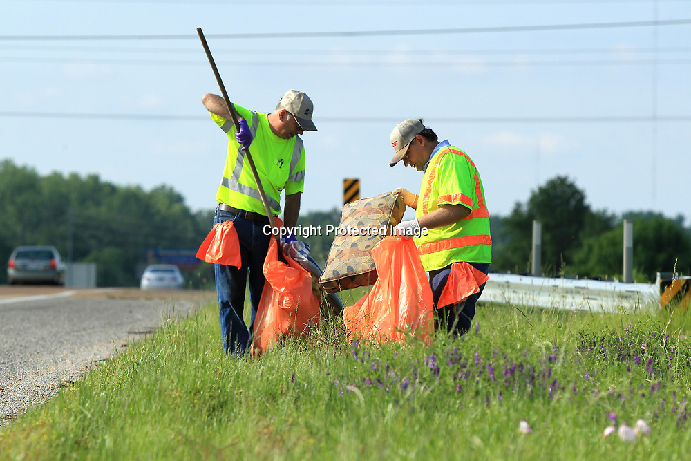 "David Smith and Donald Roberts II, maintenance workers with MDOT, pick up roadside trash on the south bound lane of Highway 45 at Main Street in Tupelo Wednesday morning. MDOT has partnered with the City of Tupelo for ""Pick it up Tupelo"", with crews out picking up litter at various intersections throughout Tupelo."
