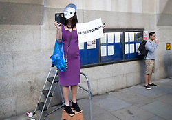© Licensed to London News Pictures . 27/09/2018. London, UK. A protestor wearing a mask depicting Tommy Robinson stans outside the Old Bailey as former EDL leader Tommy Robinson (real name Stephen Yaxley-Lennon )  starts his retrial for Contempt of Court following his actions outside Leeds Crown Court in May 2018 . Robinson was already serving a suspended sentence for the same offence when convicted in May and served time in jail as a consequence , but the newer conviction was quashed by the Court of Appeal and a retrial ordered . Photo credit: Peter Macdiarmid/LNP