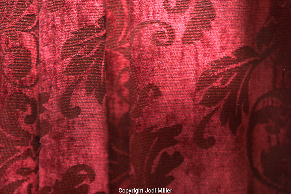 A textured velvet red curtain.