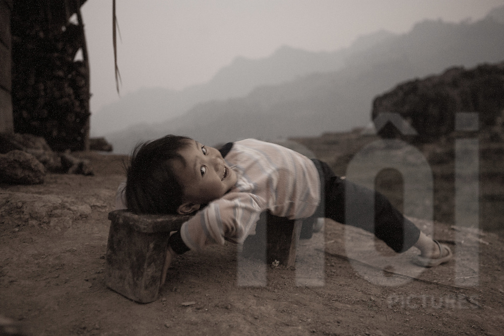 A Hmong boy stretches out on a bench at dusk. Than Uyen area, Lai Chau, Vietnam, Southeast Asia
