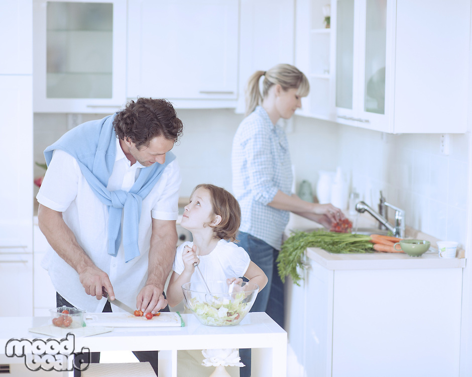 Father and Daughter looking at each other whilst preparing healthy meal in kitchen